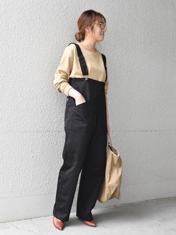 黒のサロペットに、ベージュのシンプルトップスと大きめのバッグを合わせたコーディネート。合わせるアイテムの色味を統一するだけで、落ち着いた印象に見せることができます。足元はブラウンのパンプスで、女性らしいニュアンスも忘れずに。
