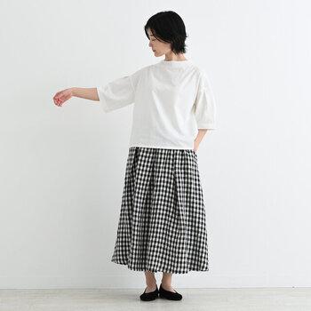 白の無地Tシャツに、ギンガムチェック柄のフレアスカートを合わせた着こなしです。足元は黒のシューズで、モノトーンコーデにまとめています。チェック柄を白黒コーデに取り入れることで、大人かわいい印象の着こなしに。肌寒い日はGジャンなどのライトアウターを羽織って、カジュアルに着こなすのもアリですね♪