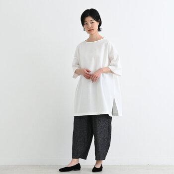 白のロング丈Tシャツを、ゆったりバルーンパンツに合わせたコーディネートです。ゆるシルエット同士の組み合わせは、スリット入りを選ぶのがバランスよく見えるポイント。ロング丈の無地Tでウエストやヒップ周りをカバーしつつ、足首見せで着やせ効果も期待できます。