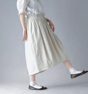 羊飼いをイメージして作られた、コットンリネン素材のスカート。裾に向かってふんわりとしぼむようなコクーンシルエットが特徴です。前後差のあるシルエットや立体感のあるヘムラインなど、ディテールにこだわりが感じられる一着です。