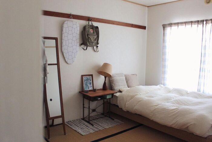 大きな掃き出し窓の横にベッドを配置すると、気持ちよく目覚められそうですね。アンティークなサイドデスクと照明が、いい味出してます。長押も収納に活用。