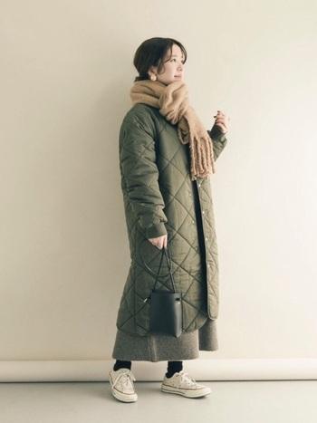 ひざ下丈のキルティングコートには、段違いのロング丈のワンピースを合わせて。コートからちらりと覗く丈感がコンパクトでバランス良しです。足元はスニーカーでスッキリとしたシルエットに。