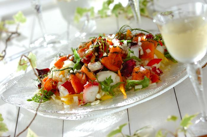 スモークサーモンやゆでダコ、パプリカなど、彩り豊かな野菜のサラダ。一皿で栄養満点です。バジルやディルなど定番ハーブが爽やかなアクセントに。