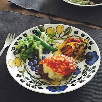 全体に柄のある大きなお皿は、料理をのせるだけでインパクトのある新鮮なイメージに。見た目がシンプルなおかずと相性が良いです。花や果実の自然を感じさせる絵柄ならナチュラルフードにも合いますよ。ランチョンマットやカトラリーは、同系色の単色にして、盛り付けたお皿を引き立たせるようにしましょう。おしゃれなテーブルコーディネートで会話もはずみそうです。