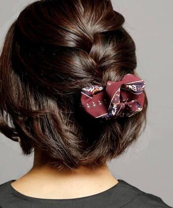 トップとサイドの髪を大きめの編み込みにしてシュシュで留めたアレンジ。シンプルなアレンジに、プリント柄のヘアアクセがワンポイントになっています。
