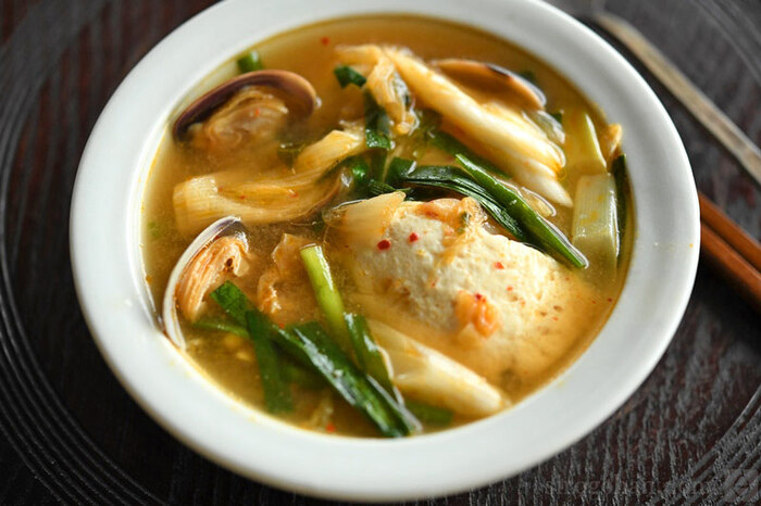 白菜キムチを使ったチゲスープのレシピです。だし汁やあさりも入った旨味たっぷりの味わい。豆腐はお好みの種類を使いましょう。白菜キムチを2回に分けていれることで、まずスープ自体に旨味を付けてから、具としても旨味を味わえるようにする(後入れなので味が抜けにくい)のがポイント♪