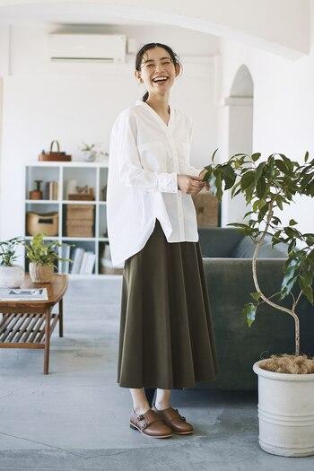カーキカラーのロングスカートに、白のVネックブラウスを合わせたコーディネートです。ふんわりと丸みのあるシルエットで、落ち着いたカラーのスカートに柔らかさをプラス。白トップスで清楚な印象を演出しつつ、大人カジュアルな着こなしにまとめています。