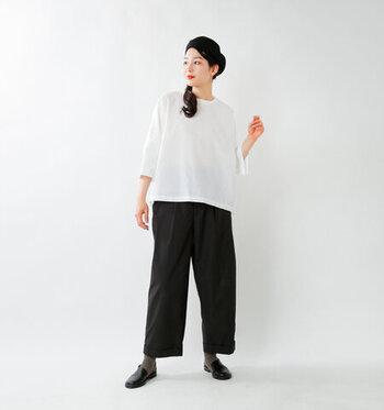ゆったりとした白のTシャツに、黒のワイドパンツを合わせたコーディネートです。シューズとベレー帽も黒で揃えて、シンプルなモノトーンコーデにまとめています。靴下にダークトーンのカーキカラーを合わせて、さりげなく差し色をプラス。