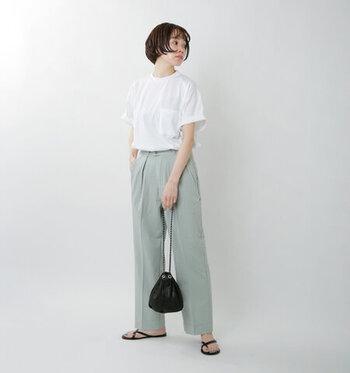ミントグリーンのセンタープレス入りパンツに、白のTシャツを合わせたコーディネートです。シンプルながらも爽やかな印象で、大人のデイリーコーデにもぴったりな装い。足元はサンダルでラフさを残しつつ、バッグとそろえたブラックカラーをアクセントカラーに活用しています。