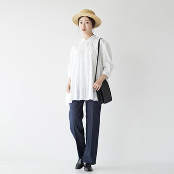 白のティアードシャツに、デニムワイドパンツを合わせたコーディネート。程よい甘さのあるティアードトップスを、センタープレス入りのデニムでクールに着こなしているのがポイントです。黒のバッグとシューズで大人っぽく決めつつ、ハットで季節感をプラスしています。