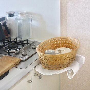 コンロひとつと小さな流し。まな板を置いての作業も苦労する小さなキッチンでは、水切りかごを置く余裕がないことも。そういう場合は、竹製のかごを水切りかご代わりに活用してみて。タオルハンガーを起こして、一時的なかご置き場に。一人暮らしならではの臨機応変な暮らし術です。