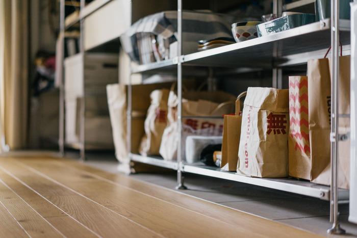 一人暮らしの部屋だと、スペックがカチッと決まってしまう食器棚より、汎用性が高くて、いろんなものを収納しておける棚の方が、使い勝手が良いもの。食器は安全と見やすさを考えて並べて収納がべター。食器以外のものは、カゴやストレージボックスに入れて雑多に保存というのもいいけれど、スペースをとりすぎてしまうという場合は、紙袋を有効活用するという手も。無印などクラフト紙のものなら、素朴で統一感もあります。