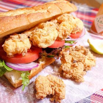 """フランスパンにシーフードのフライや野菜を挟んだサンドイッチ「ポーボーイ」は、""""プアボーイ(貧しい少年)""""からきた名前といわれています。値段が安いので貧しい人が食べていたのだとか。でも、その名とは違ってとてもおいしくて風味豊かです。"""