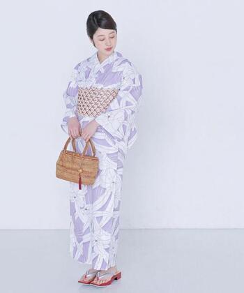 薄紫に大きくカトレアの花が描かれた可憐な浴衣には、思い切って全体に模様が入った古典風の帯を合わせると、浴衣を着なれている上級者のコーディネートになります。帯の柄の色やかごに付けた小物、そして草履の色がすべて同じカラーリングなので、まとまりのある大人なコーディネート例です。