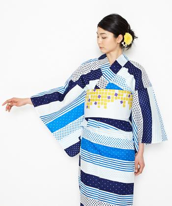 浴衣の柄と帯の柄を幾何学模様でまとめたコーディネート。ヘアのお花のカラーリングも帯に合わせて大胆不敵に。