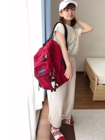 リュックと靴下をリンクさせて、差し色にしています。白のワントーンコーデに赤をプラスした、バランスのいい素敵なコーデですね。