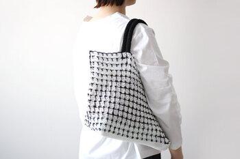 こちらは4本撚りのプラコードを使ったモノクロかごバッグ。プラスチック素材で耐水性があるので、急な雨やレジャーシーンで使うのも気楽。白黒のコントラストが浮かび上がる模様編みがとても洒落ています。