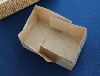 紙袋の真ん中で切り、収納ケースのサイズに合わせます。