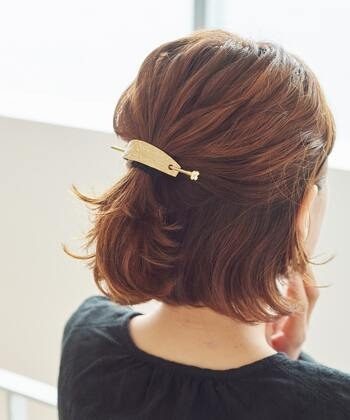 耳上の髪の毛を手ぐしでざっくりまとめたら細めのゴムで結びます。トップ部分をほどよく引き出してバランスを整えたら、結び目にマジェステをオン。肌馴染のよいゴールドのバマジェステが聡明な印象を与えます。