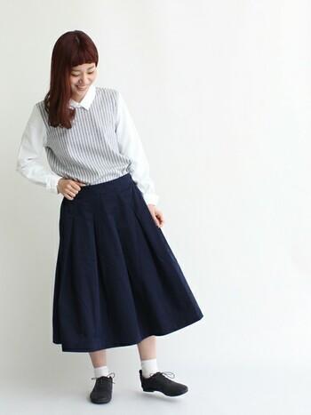 グレーのストライプ生地とシャツ生地がドッキングした変わり種シャツ。綺麗な形のスカートと合わせれば、大人の優等生コーデに。白を取り入れる場合は2つのアイテムで色を揃えて、まとまりのある印象に。