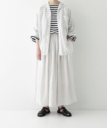 白のリネンシャツを、同素材のスカートと合わせたセットアップ風コーデ。透け感のあるシャツなので、トップスのボーダー柄が程よいアクセントになっています。足元は黒のサンダルで、ナチュラルなモノトーンコーデに。