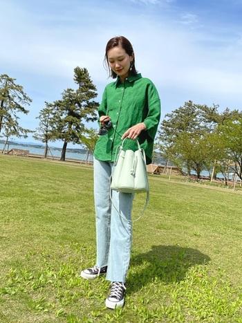 パッと目を引くグリーンのリネンシャツに、デニムパンツを合わせたシンプルなコーディネートです。スニーカーでカジュアルにまとめつつ、大人っぽさを演出できるデザインのショルダーバッグをチョイス。薄いブルーのデニムが、春夏らしさを感じさせる着こなしですね♪