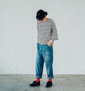 ボーダー柄のTシャツに、デニムパンツを合わせるカジュアルなコーディネート。デニムパンツはあえて裾をロールアップして、赤の靴下をちらりと覗かせています。黒シューズとの対比で、赤がはっきりとわかるのもポイントのひとつ。シンプルコーデには、カラー靴下でアクセントをプラスしましょう。