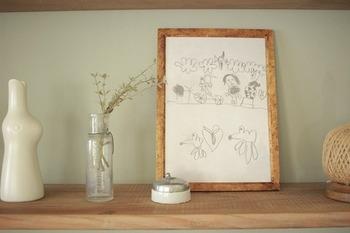 こちらはらくがき帳に描いた絵を木のフレームに入れているそう。フレームの素材を他のテイストと合わせるとナチュラルにマッチします。