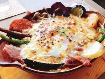 こちらは「王様焼きカレー」。オーナーシェフが野菜ソムリエということもあり、旬の野菜が器を囲むようにずらりと並びます。チーズの下には卵が隠れているんです!カレー、チーズ、卵を一緒に食べると、やみつきになりますよ。