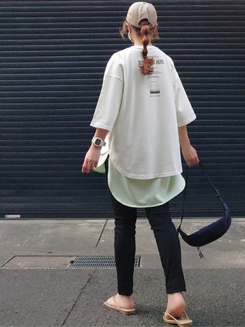 黒のデニムパンツに、半袖Tシャツを2枚レイヤードしたスタイリングです。グリーンのロング丈Tシャツの上に白のロゴ入りTシャツを重ねて、トレンド感をしっかりと押さえた着こなしに。ヒップラインが隠れるので、体型カバーにも最適なコーディネートですね。
