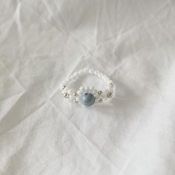 存在感のある石のようなビーズをあしらった、宝石リングのデザイン。白とシルバーのベースは軽やかで品の良いスタイルになりますね!