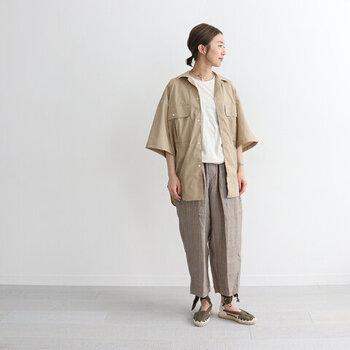 さりげないストライプ柄のワイドパンツに、白トップスとベージュのシャツを合わせたコーディネート。羽織りとボトムスの色の系統を合わせているので、柄パンツが浮いて見えないのがポイントです。足元はサンダルで、涼しげな印象をアピール。ナチュラルなカジュアルコーデの完成です。