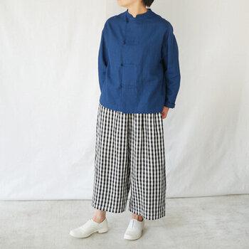 どんなトップスにも合わせやすい、モノトーンのチェック柄パンツ。ブルーのブラウスとシンプルな着こなしで、ナチュラルなスタイリングにまとめています。足元は白のシューズで、爽やかさをアピール。