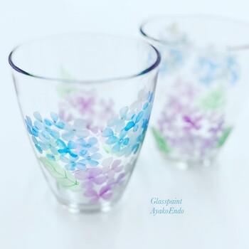 テーブルに季節感を添えるなら、あじさい柄のグラスはいかがですか? ひとつひとつ手描きで絵付けされたあじさいは、透け感のある色が魅力的。サイダーやレモンウォーターなど、爽やかな飲み物を注ぎたくなりますね。  夜はキャンドルホルダーとして使用しても素敵。色違いの白いあじさい柄と揃えたくなりますね。