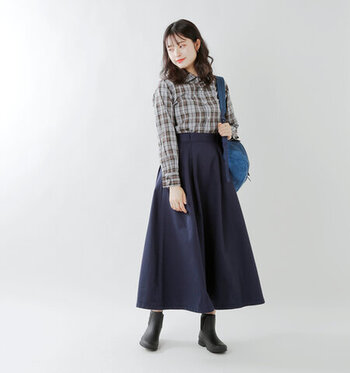 チェック柄のシャツにAラインスカートという、レディライクな落ち着きのある装いです。足元にはショート丈のレインブーツを合わせてバランスよく。