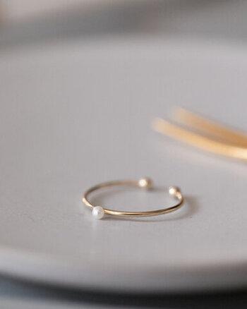華奢なゴールドの輪の上に、水滴のような淡水パールがちょこんと乗ります。3号から5号までのサイズ調節が可能な、フリーサイズのピンキーリングです。シンプルなデザインで重ね付けにもおすすめ。