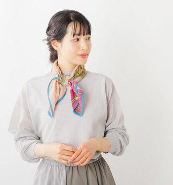 発色がよく色彩の豊かなスカーフは、ネックレス感覚でアクセサリー代わりとしても活躍します。首元にふんわりと結んであげるだけで、シンプルなコーデも華やかなイメージになりますね。