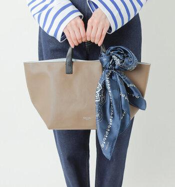 バッグに添えるスカーフの色を、洋服と合わせるのもおしゃれ♪ 大柄のスカーフは、巻き方やたたみ方で柄の出方が変わるので、その日の気分や服装に合わせて変えてみるのも楽しいですよ。
