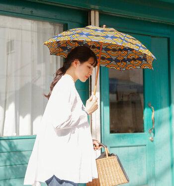 アフリカンバティックを使用し、鮮やかな色彩と大胆なモチーフが目を惹く長傘は、日の光に負けない存在感があります。