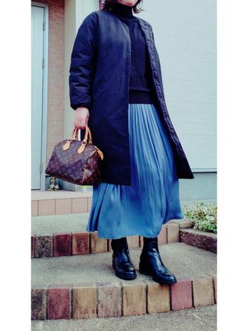 艶やかな生地&きれいなブルーのスカートが主役のコーデには、すっきりとしたダウンコートで縦ラインを強調。 足元は、ダウンコートに合わせて軽くなりすぎないように、ボリュームもあるブーツで決めて。  アイテム選びによって差し引きのバランスが抜群。オシャレ上級者のコーディネートです。