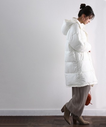 目をひく真っ白なダウンコートには、やわらかな色味のベージュボトムをのぞかせて。 軽やかなカラーのダウンでしっかりと防寒したほうが冬コーデはスマートに決まります。足元も、ちょっぴりヒールのあるショートブーツで大人っぽく決めて◎