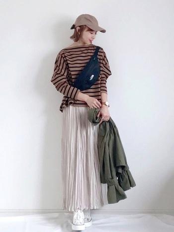 光沢のあるロングタイプのプリーツスカートには少しボーイッシュなアイテムをプラスしてみると◎
