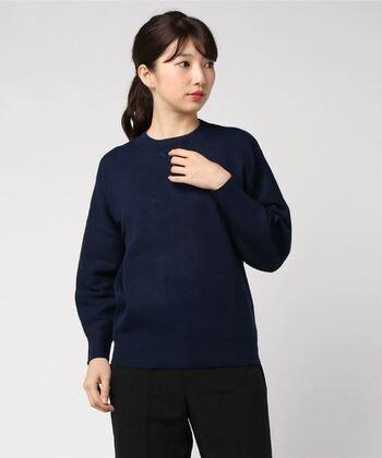 襟ぐりと裾、そして袖口にリブが入ったネイビーニットは、体にフィットしすぎず柔らかなラインなのでどんなボトムスにも合わせやすい。