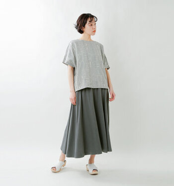 洗いがかったような優しい風合いのコットンを使用したロングスカート。長すぎず短すぎない程よい丈感でバランスが取りやすく、裾に向かって流れるフレアーのドレープが美しい一枚です。