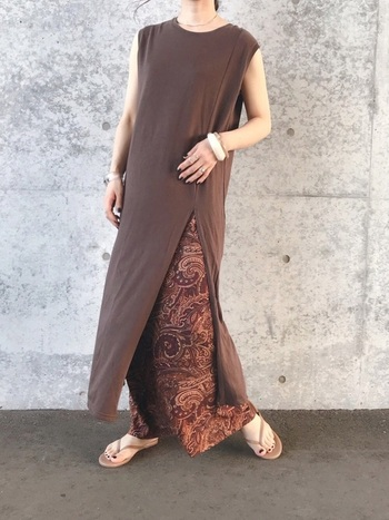 大胆なスリット入りのロングワンピースに、マキシタイトスカートを重ねたレイヤードスタイル。エスニック柄も同色系&チラ見せすると洗練された印象に。足元はサンダルで抜け感を出し、太めのバングルでアクセントをプラスしています。