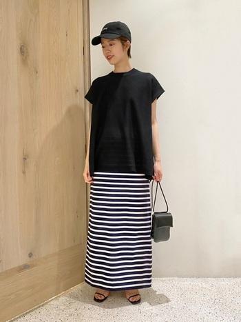紺色ボーダーのロングスカートに、大きめの黒Tシャツを合わせたカジュアルコーデ。濃いめのトップスが引き締め役になっていて、小さめバッグとサンダルでバランスを上手に取っています。