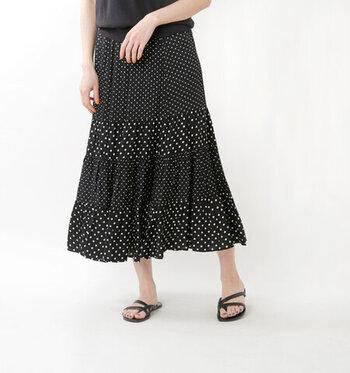 光沢感のあるサテン素材を採用し、歩くたびに揺れて優雅さを演出してくれるスカート。ドットプリントとティアードデザインが印象的で、シンプルなトップスに合わせても個性を演出できる一枚です。モノトーンカラーながらも華やかさを演出してくれます。