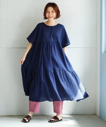 アキハと呼ばれる、波打つような柄が特徴的な織物を生地に採用した、ティアードワンピースです。2段の切り替えで、ボリューム感たっぷりに仕上げたゆったりシルエットが特徴。程よく透け感があるので、ペチコートを合わせてワンピースとして着たり、パンツやスカートを重ねたりするレイヤードコーデがおすすめです。