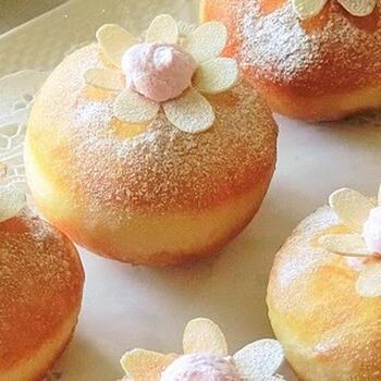 フレッシュな苺クリームがたっぷり入ったドーナツ。最後に、表面に苺クリームをひと絞りして、アーモンドスライスを花びらのように飾ります。素敵なアイデアですね。