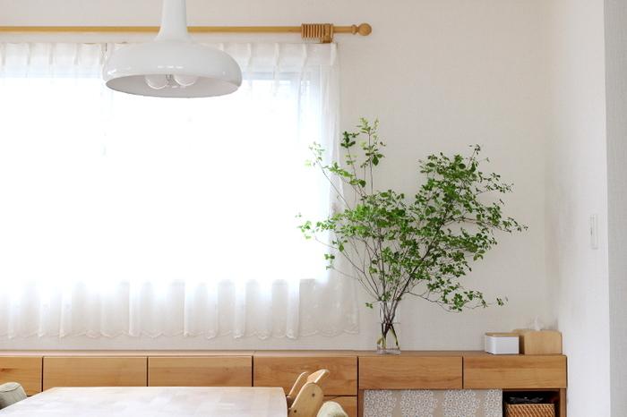 ダイニングテーブルのすぐ近く、家族みんなの目に入る場所に棚に飾った「ドウダンツツジ」。ここなら、食器の邪魔にもならず、小さい子どもが食事中に触れてしまうこともありません。  白い壁に深緑の葉がよく似合っています。